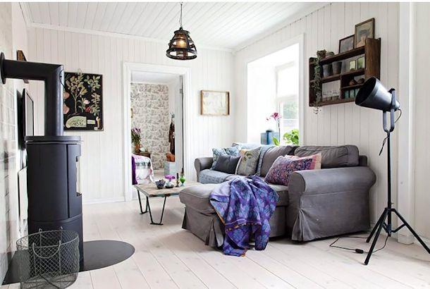 Living con sillón gris generando contrastes con el blanco de la madera