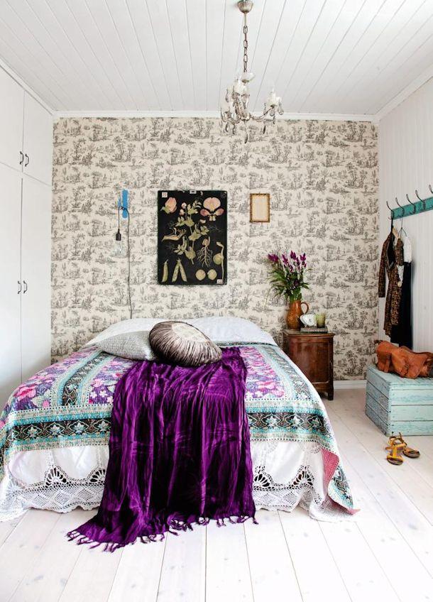 Dormitorio rústico con pared empapelada funcionando como respaldo de cama
