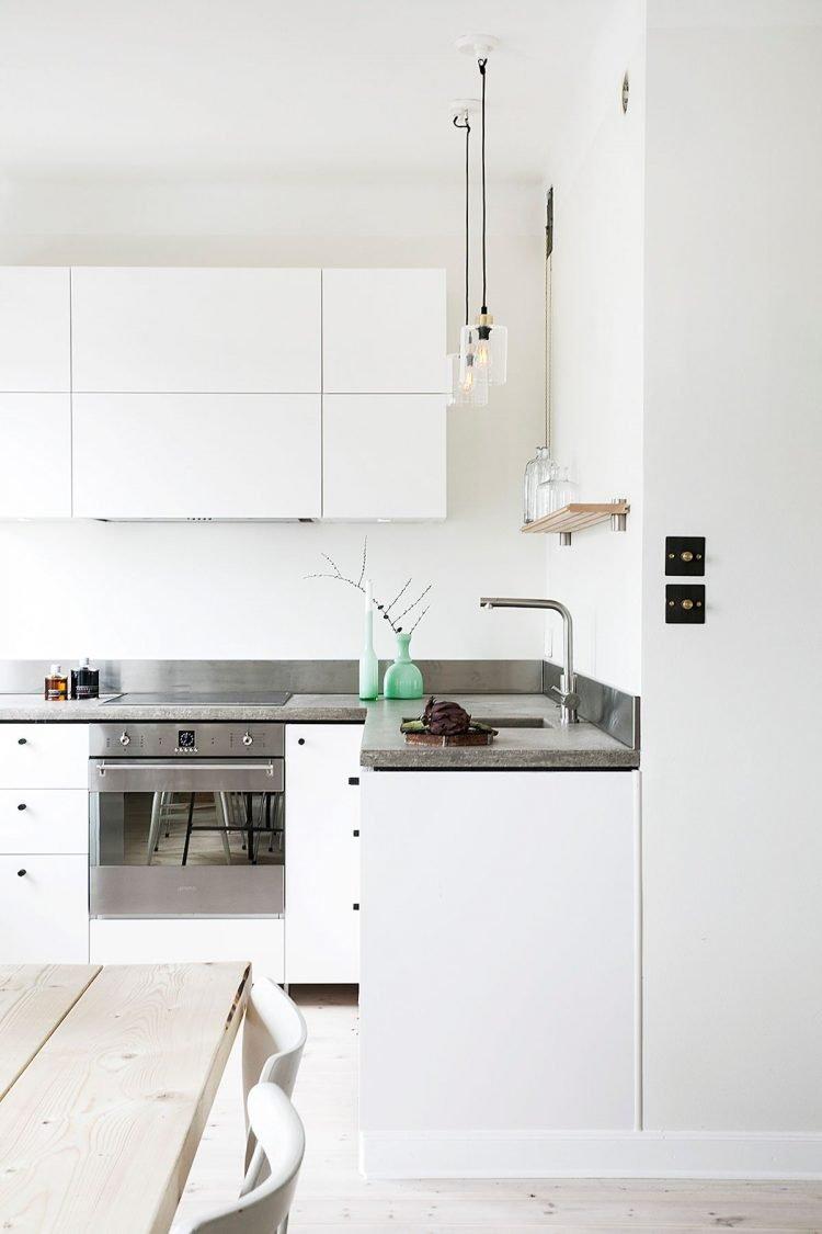 Muebles de cocina blancos y encimera de concreto pulido