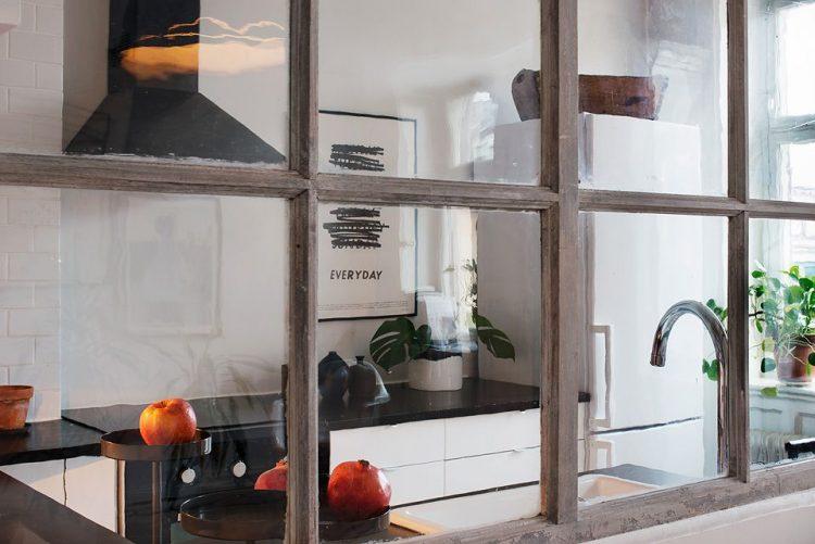 Una ventana instalada en la pared que divide la cocina de la sala ayuda a que la cocina se sienta menos encerrada y al paso de luz natural