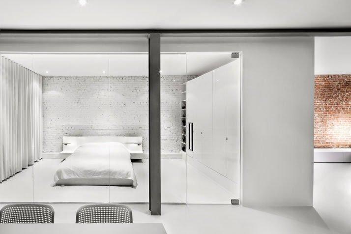 Recámara con decoración minimalista y pared de vidrio que separa e integra a la vez