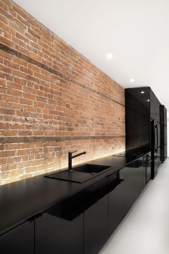 Cocina con muebles negros y pared de ladrillo a la vista