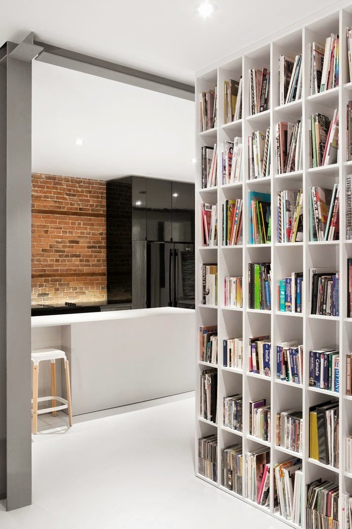 Los libros exhibidos en el librero añaden color de forma natural al espacio minimalista