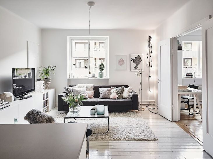 La paleta de color del living se limita al blanco, el gris del sofá y el color que aportan los pisos de madera clara
