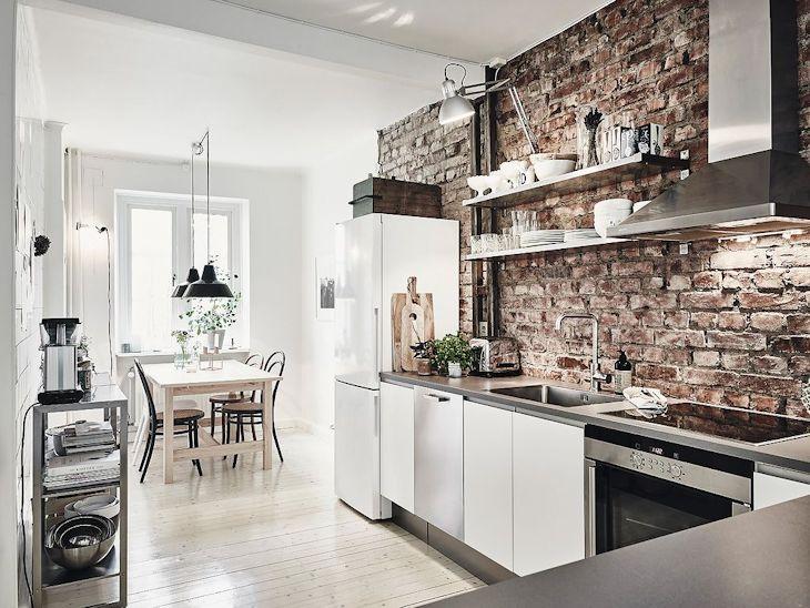 En la cocina se dejó una de las paredes con ladrillo visto, sumando color a la decoración y aportando una estética industrial
