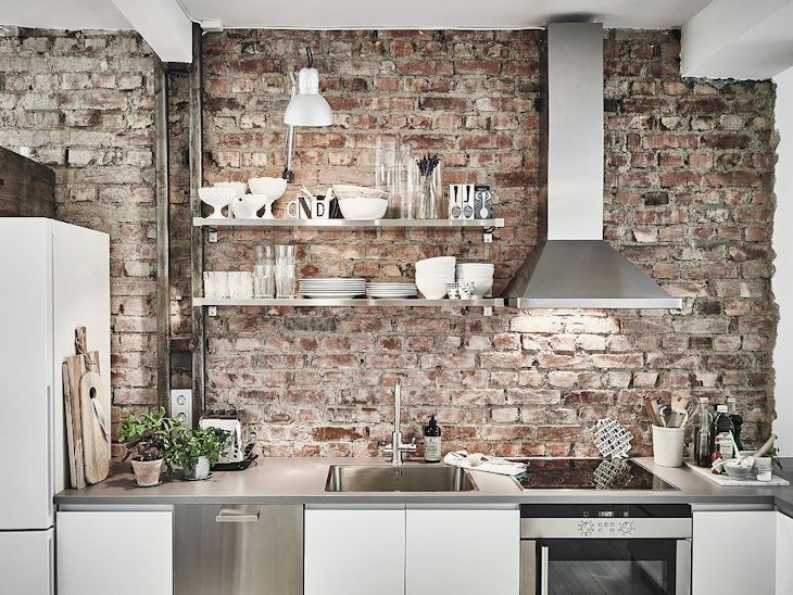 La pared de ladrillo visto combina muy bien con el acero inoxidable de los artefactos de cocina, la pileta, la campana y las estanterías