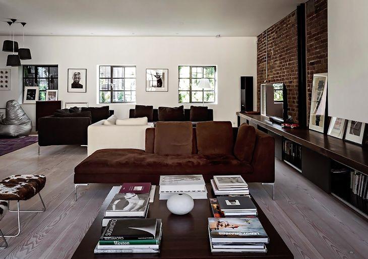 Sala estilo industrial dividida en dos espacios: sala de reuniones y sala familiar para mirar TV