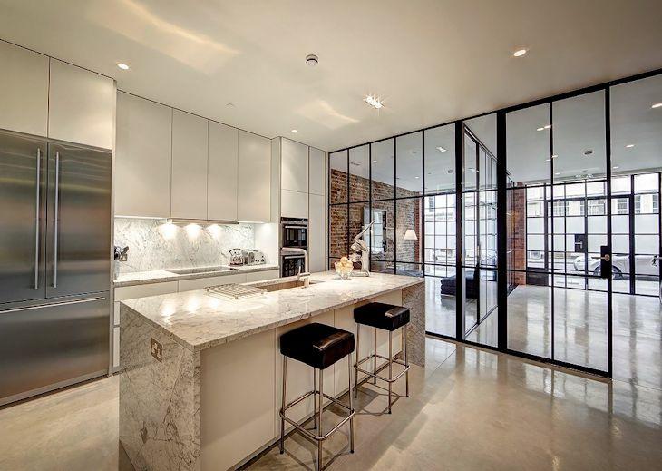 Cocina moderna e industrial en la planta baja, con separación vidriada