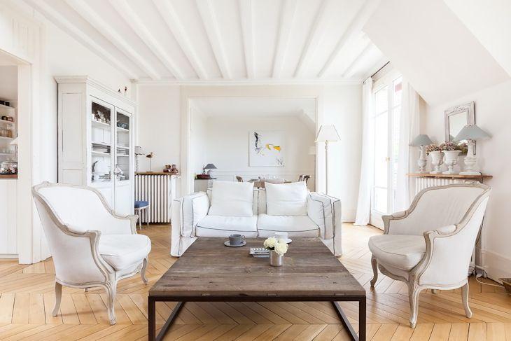 Sillones individuales clásicos, un sofá actual y una mesa de centro rústica forman el área del living