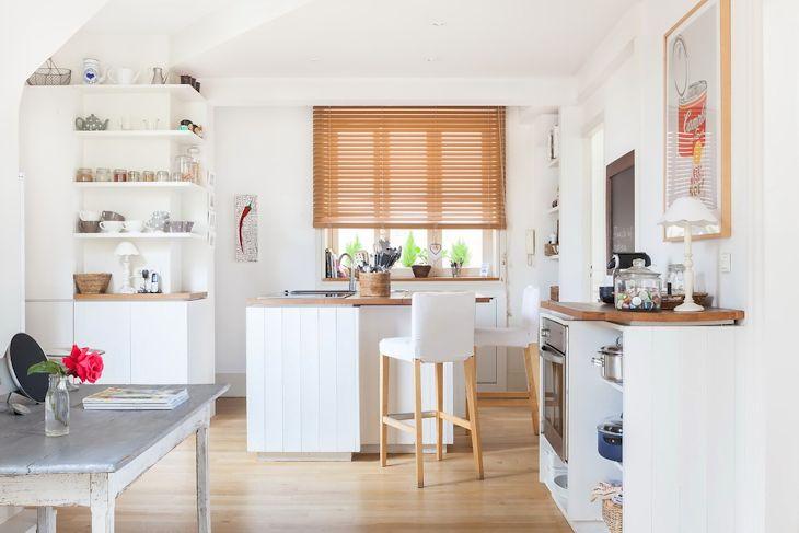 Cocina renovada con mesada de madera tratada y muebles de madera pintados de blanco