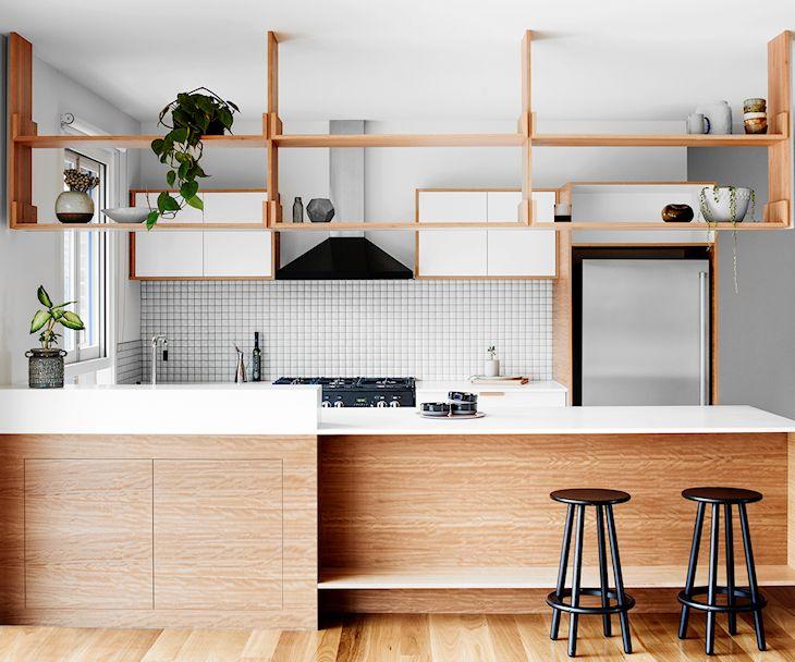 Cocina con barra de madera y muebles con puertas blancas y estructura de madera