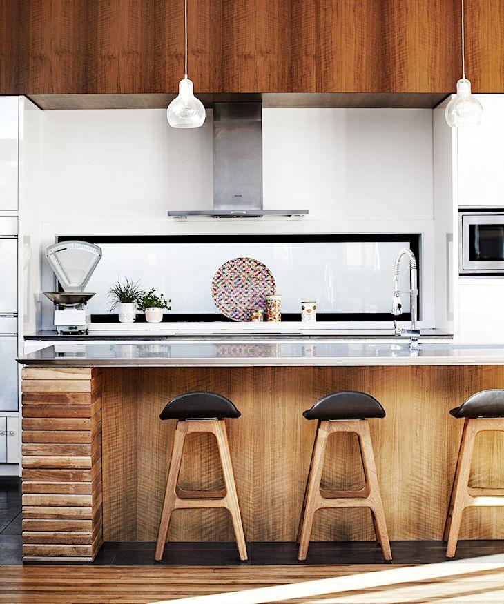 Cocina con mesada de acero inoxidable y mueble terminado con diferentes tipos de madera