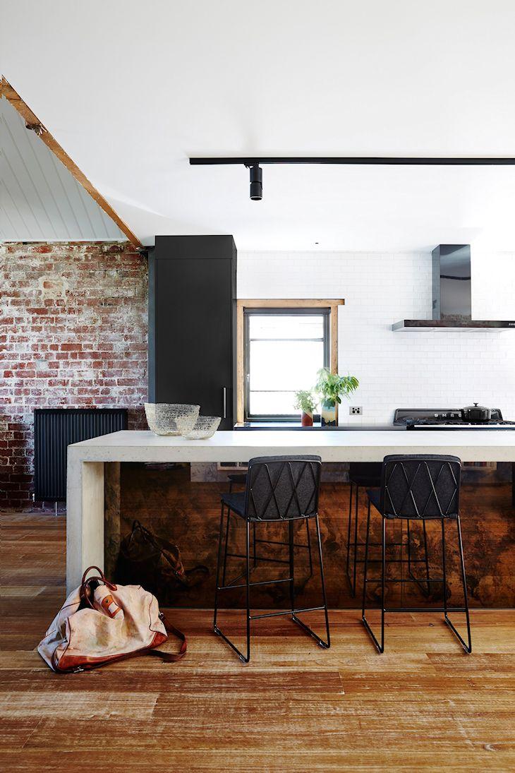 Diseño de estilo industrial en una cocina que combina la madera con paredes de ladrillo visto y cemento alisado