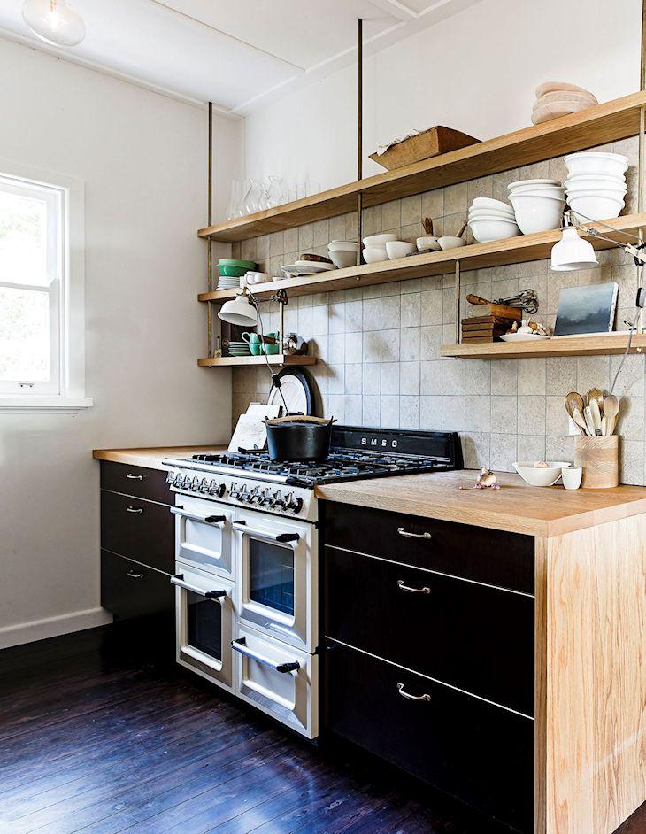 Cocina pequeña con estantes de madera y muebles de cocina con mesada de madera y cajones pintados de negro