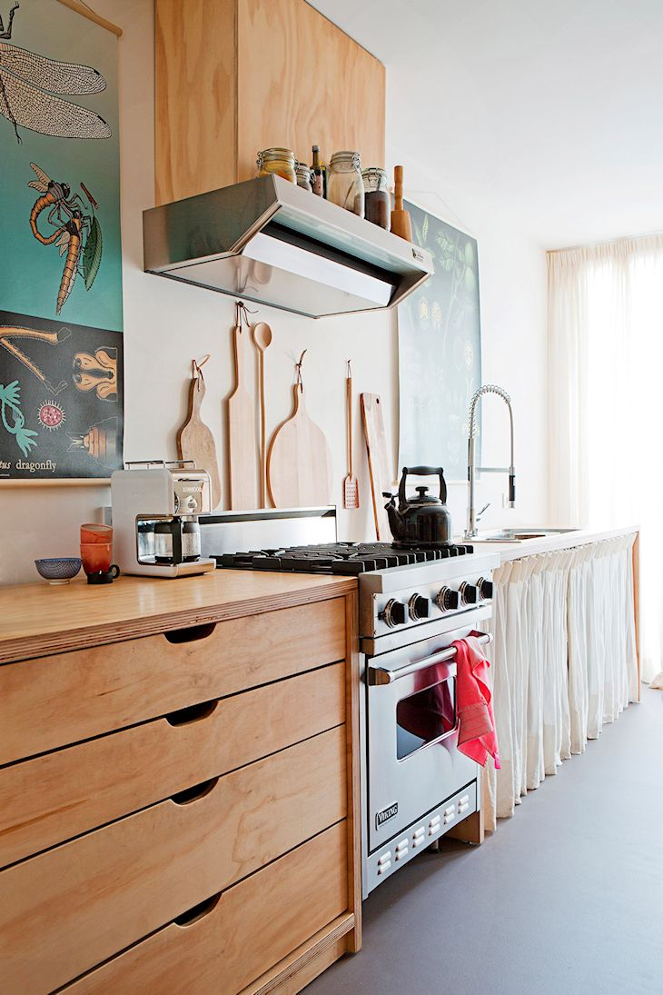 Cocina de líneas económicas con un mueble con cajones y mesada de madera