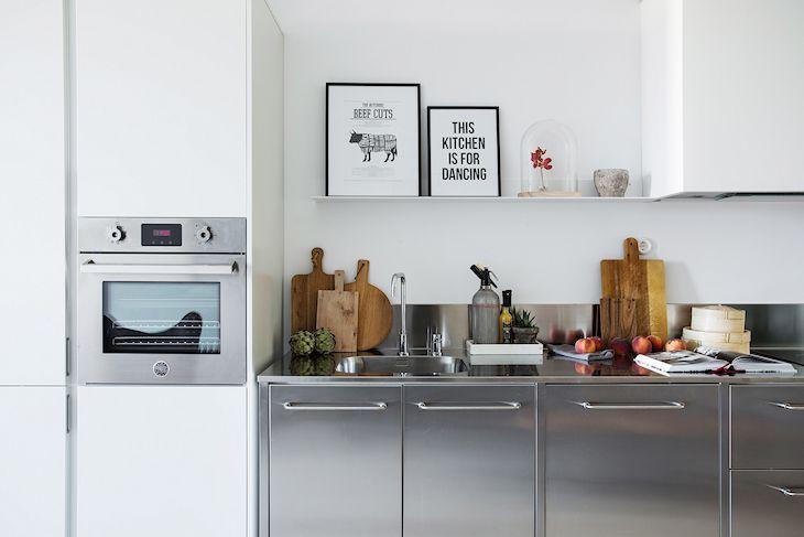 El blanco y el gris del acero dan la pauta neutra de color a la decoración de la cocina y el ambiente principal