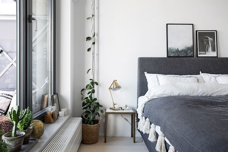 Respaldo y base de cama tapizados en tela gris jaspeada con sábanas blancas y cubrecamas gris