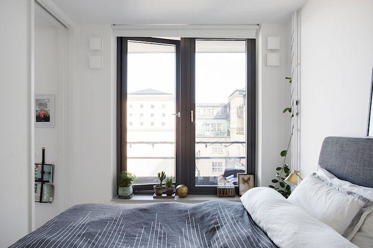 Los textiles se adaptan a los colores básicos del dormitorio: paredes blancas y ventanas en gris