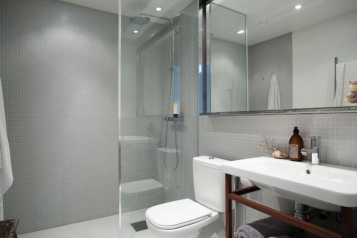 Baño con revestimiento de venecitas grises en las paredes y venecitas blancas en el piso