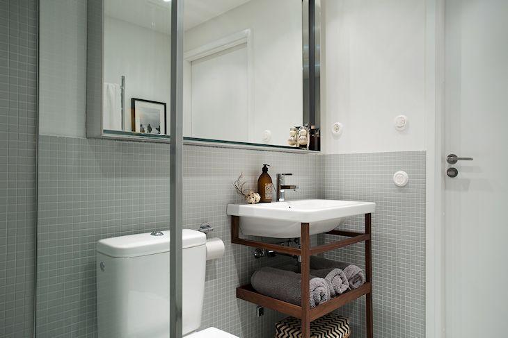 Vanitory en madera con espacio de guardad, espejo y mampara con bordes de acero inoxidable