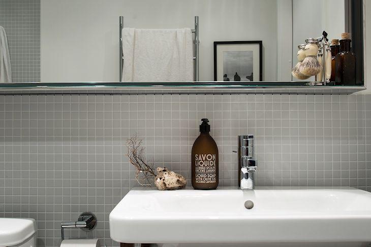 El baño repite la paleta de color del resto del departamento: gris y blanco