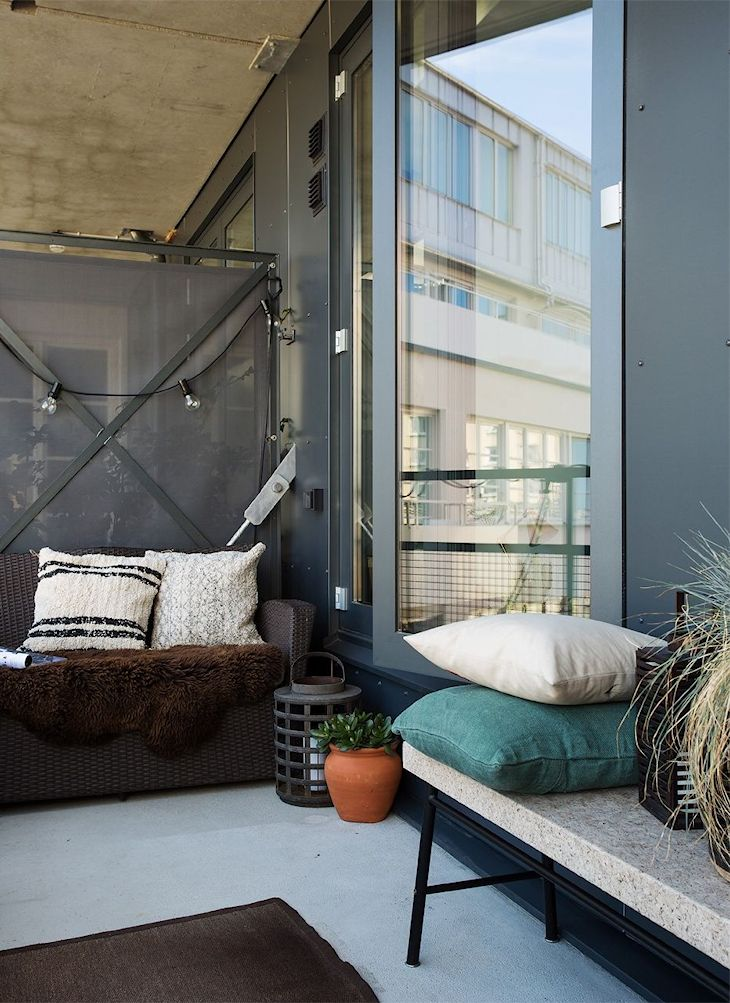 Un sillón de ratán sintético se ubica en un extremo del balcón, suavizado con almohadones en variadas telas, colores y texturas