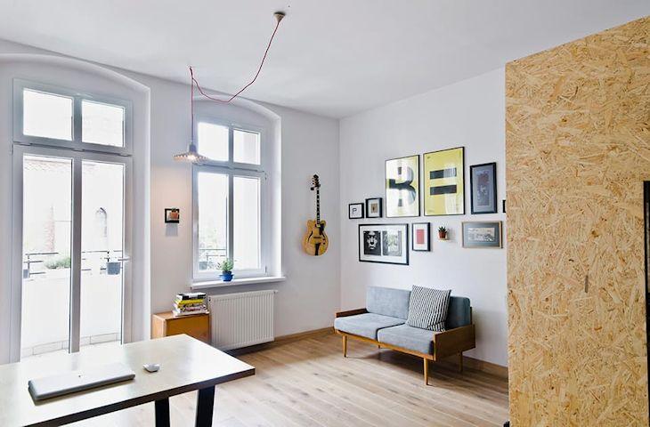 Living del estudio con un pequeño sillón estilo vintage y muchas láminas para dar color a la decoración