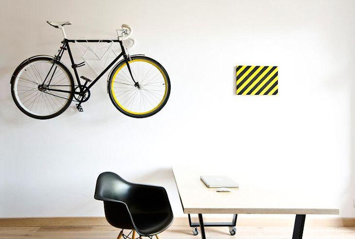 Bicicleta colgada en la pared del estudio para aprovechar el espacio