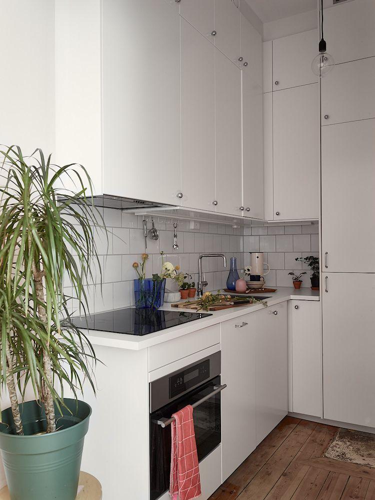 Cocina pequeña estilo escandinavo con muebles, alecenas y azulejos blancos,