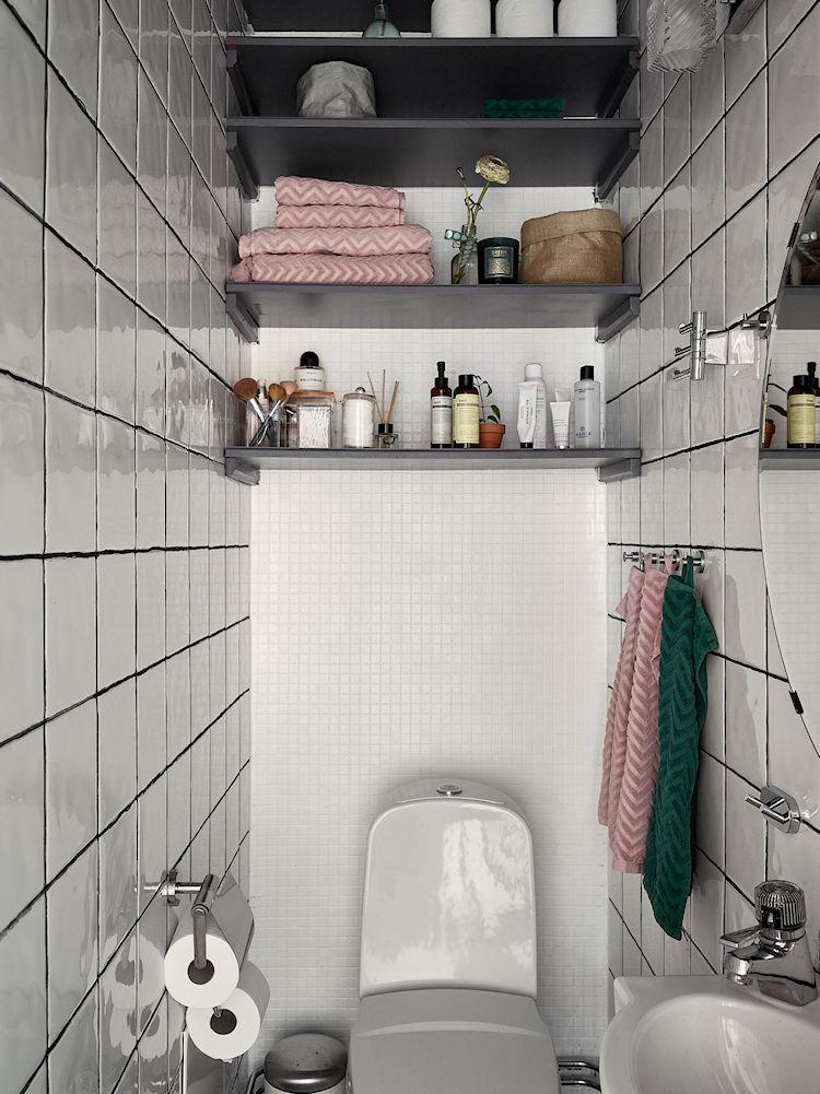Baño muy pequeño en blanco con estantes grises para sumar espacio de guardado