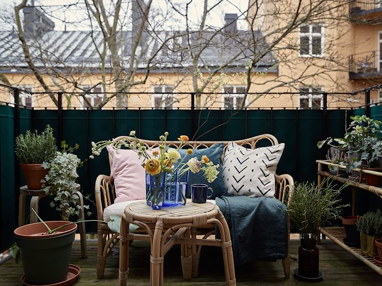 Balcón pequeño decorado con plantas en macetas y muebles de exterior de mimbre.