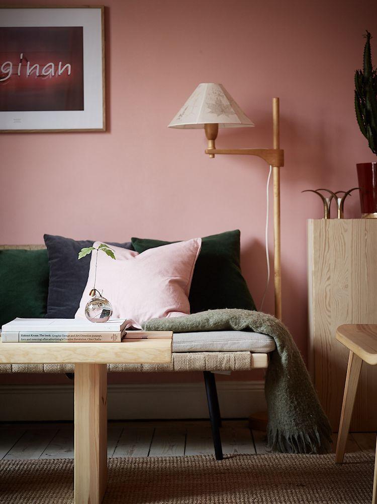 Para contrarrestar el rosa de las paredes, los textiles de la sala son en colores diferentes, como los cojines verdes y grises oscuros.