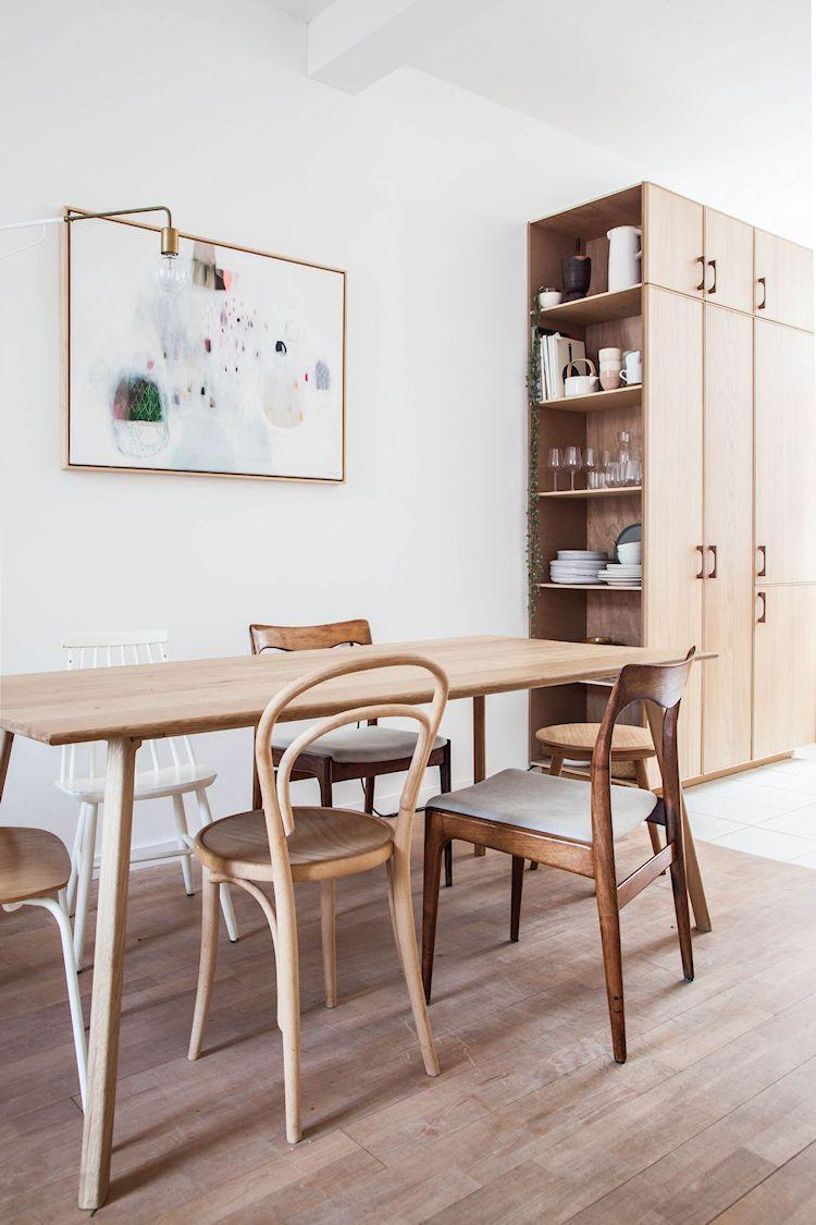 Comedor con mesa de madera y sillas en diferentes estilos