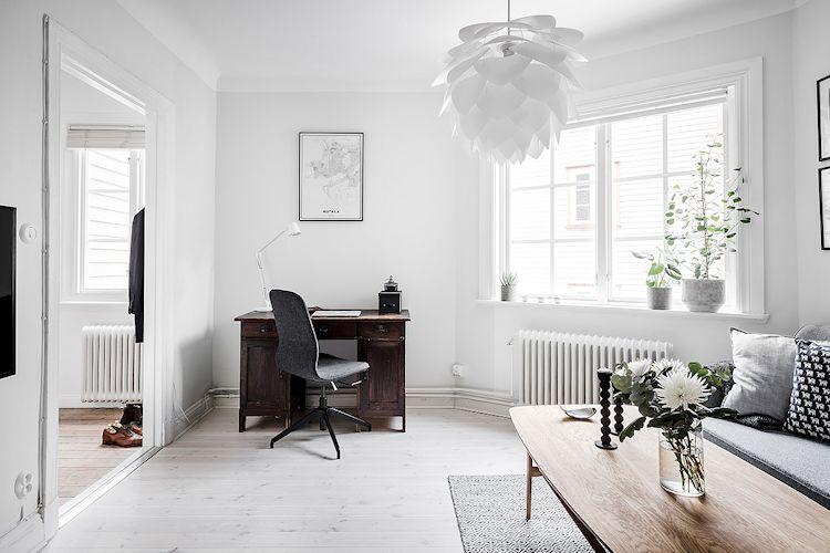 Un escritorio antiguo en un rincón configuran un espacio de trabajo cómodo, funcional y con mucha luz natural.