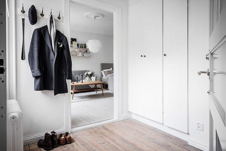 En el hall, la puerta que lo comunica con la sala se ha quitado para ahorrar espacio. Los pisos de madera natural lo diferencian de la sala.