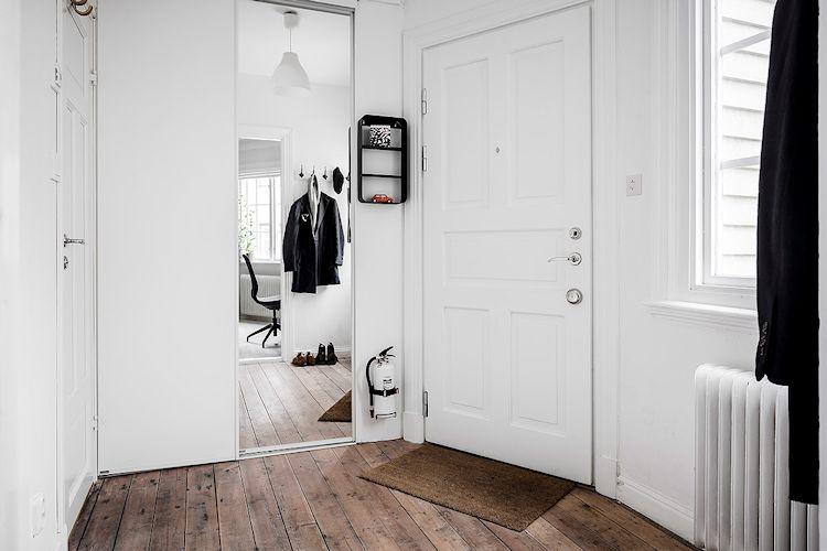 Puerta de acceso al departamento y clóset con puerta espejada.