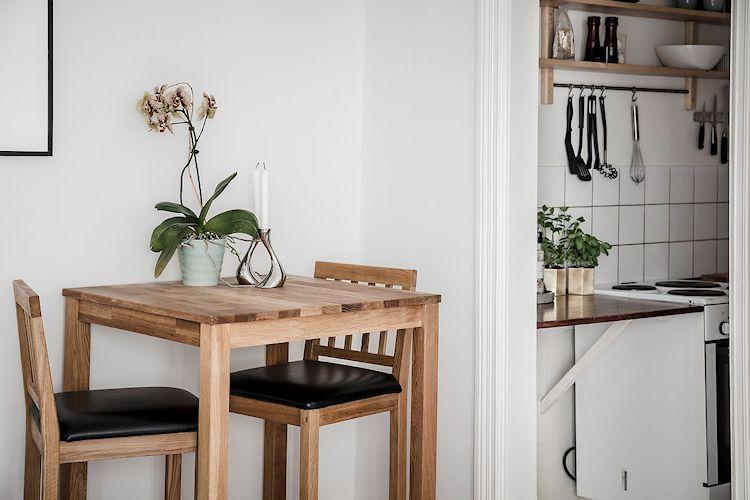Comedor pequeño con mesa y sillas altas. La altura de los muebles hace que el comedor resalte y se diferencie del resto del ambiente de forma natural.