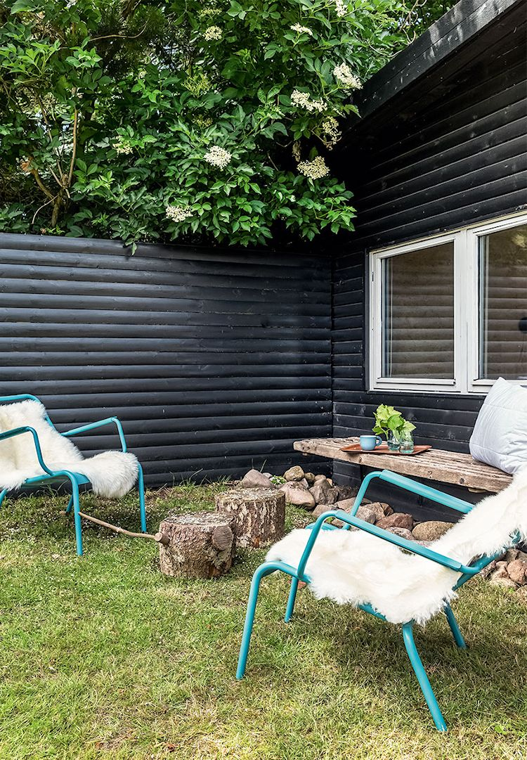 Sala al aire libre. Los pocos metros interiores se compensan con espacios exteriores amplios. El revestimiento pintado de negro es muy común en los países escandinavos.