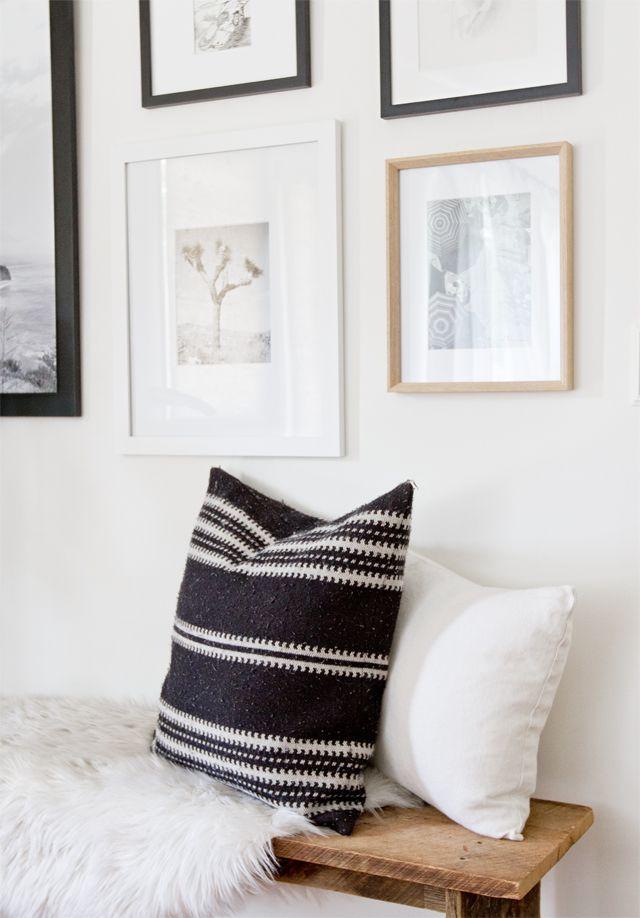 La banca de madera rústica combinado con los cojines y la manta aportan calidez a la decoración e invitan a quedarse en la sala.