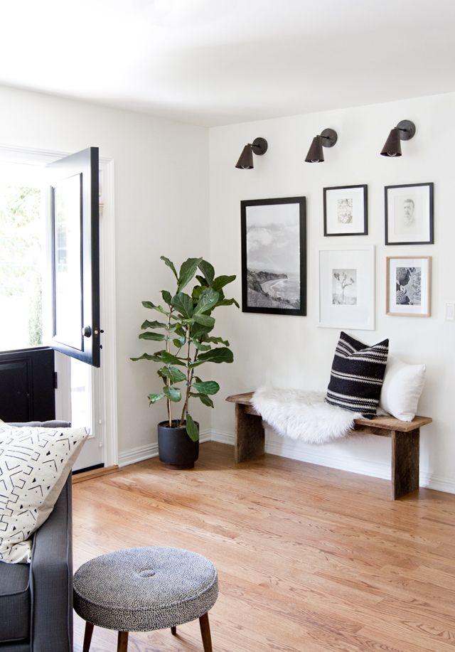 Lámparas de pared y conjunto de cuadros sectorizan el espacio junto a la entrada. Un Ficus lyrata aporta color.