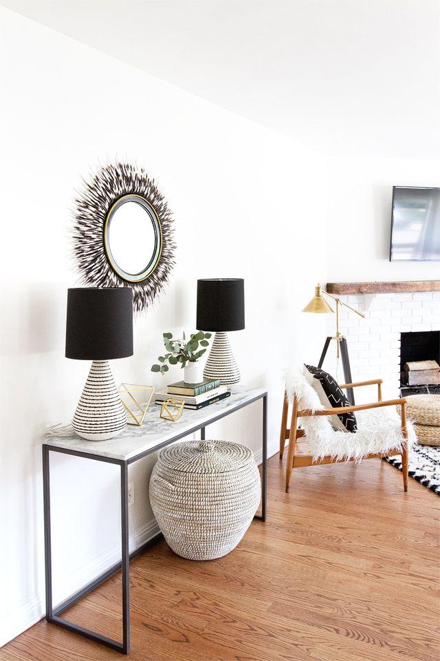 Una consola con lámparas, objetos decorativos y un llamativo espejo redondo ocupan un lugar vacío y complementan la decoración de la sala.