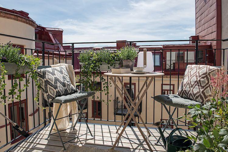 En el balcón se armó un comedor con dos sillas y mesa pequeña plegables de metal.
