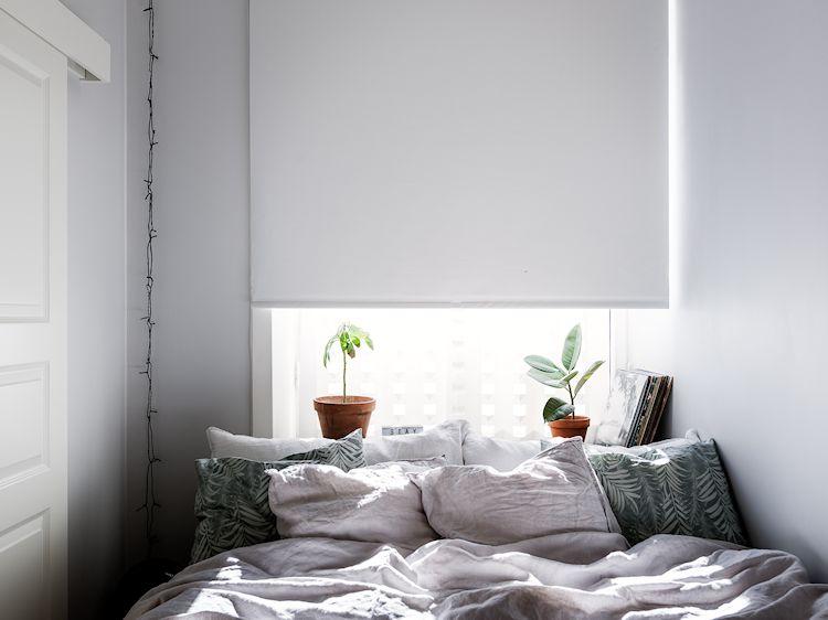 En la recámara pequeña minimalista la base de la ventana hace de buró y de cabecero de cama