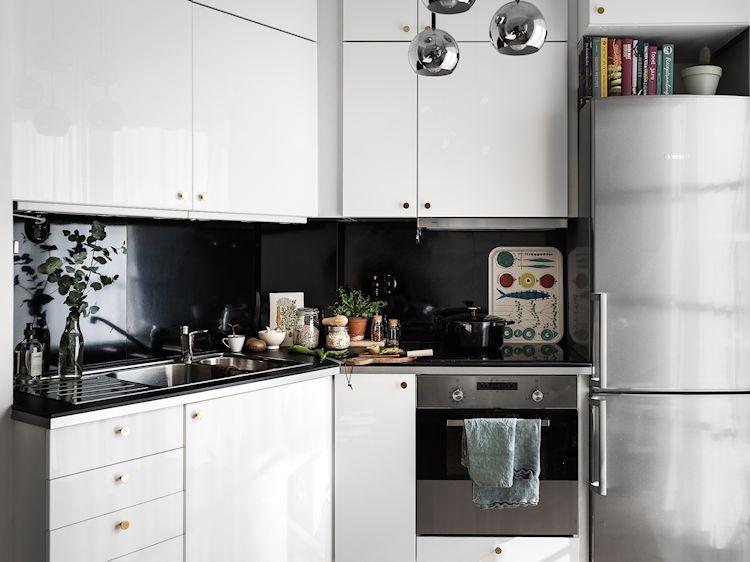 Muebles de cocina blancos con detalles en negro generan la clásica combinación de colores que se ven en viviendas de estilo escandinavo