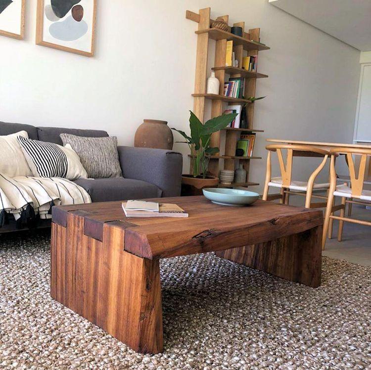 Mesa de centro de madera rústica, tapete de fibras naturales y un sofá gris decoran la sala del departamento