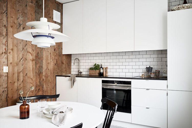 Pared revestida en madera junto a la cocina para sumar calidez a la decoración