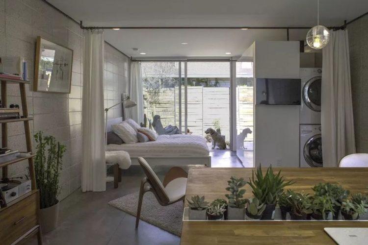Riel con cortinas instalado en el techo separan la recámara y las lavadoras de la sala
