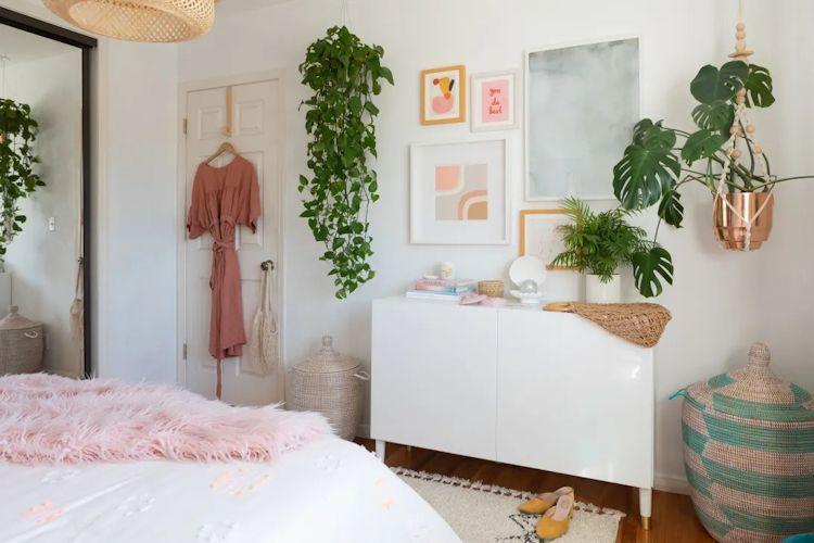 Conjunto de cuadros sobre la pared y muchas plantas crean un espacio muy acogedor en la recámara
