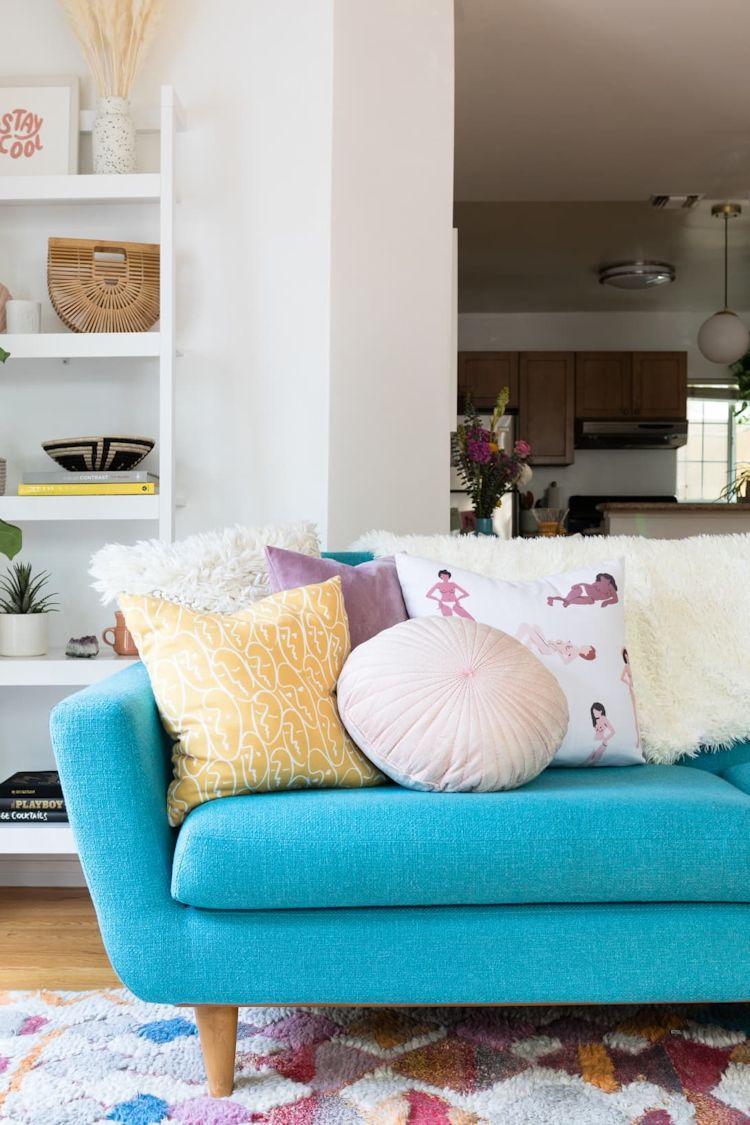 Sala con sofá turquesa y muchos cojines, elementos que suman colores y texturas a la decoración