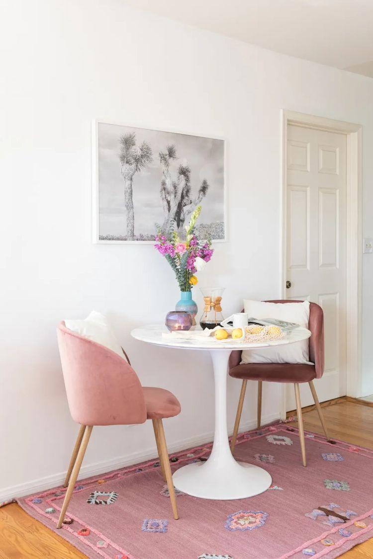 Comedor en área de circulación que une sala y cocina. El tapete rosa ayuda a sectorizar el espacio.